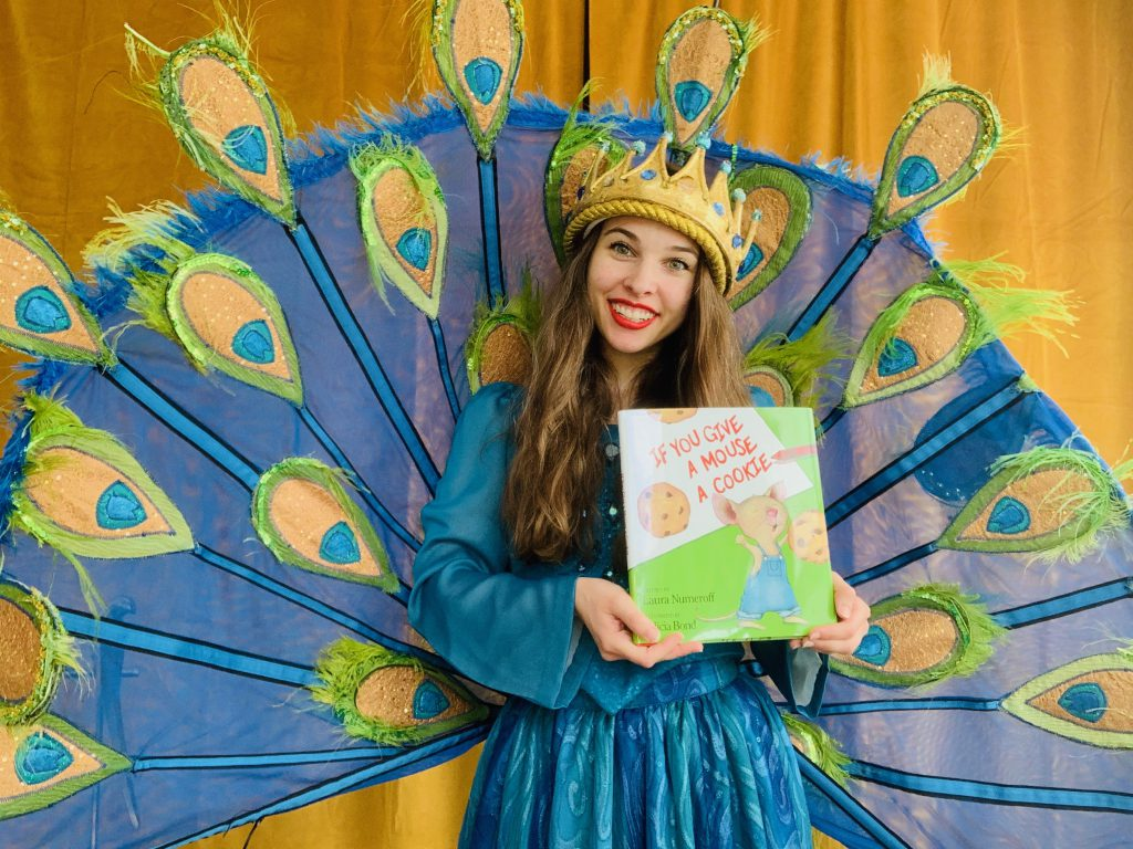 Penelope Princess of the Peacocks holding a children's book.